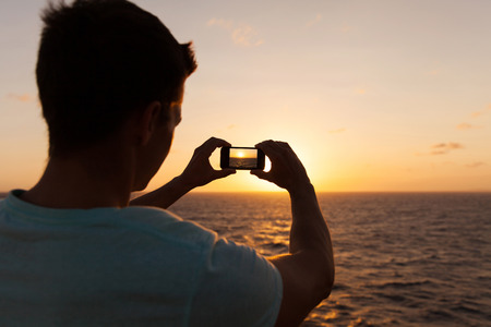 over the sea: man taking picture of beautiful sunset over sea