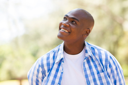 cheerful young african man looking up