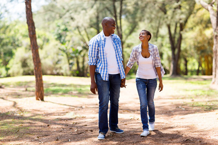 boy and girl holding hands: happy african couple enjoying a walk at the park