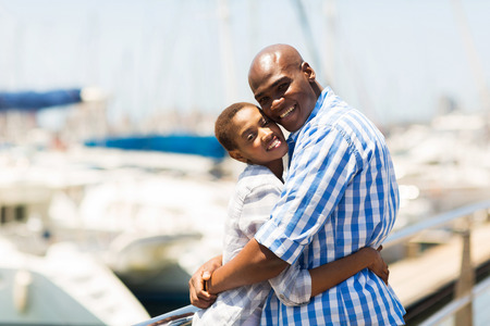 cute young black couple hugging at the harbor photo