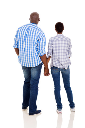 holding back: rear view of young african couple holding hands isolated on white background Stock Photo