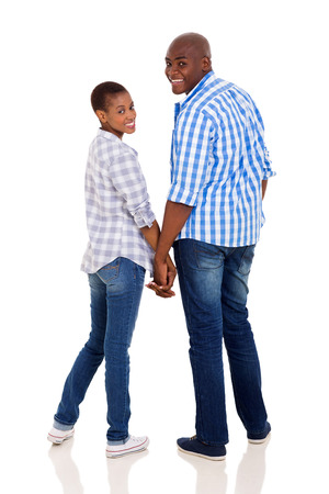 cute young african couple holding hands and looking back isolated on white photo
