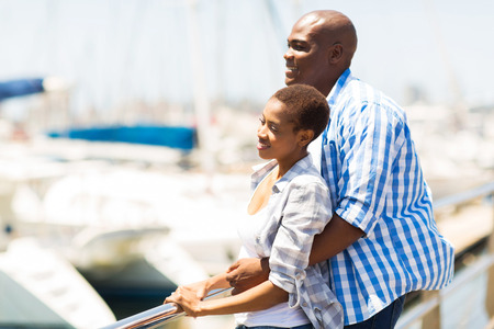 cute young african american couple daydreaming at the harbor photo
