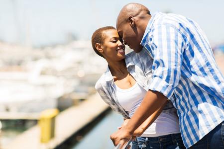 parejas felices: encantadora pareja afroamericana besar en el puerto Foto de archivo