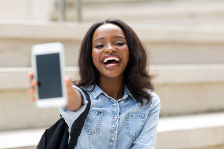 woman holding bag: cheerful female university student showing smart phone Stock Photo