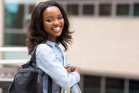 souriante jeune étudiant universitaire africain maintenir les livres