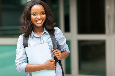 tertiary: attractive female afro american student holding books