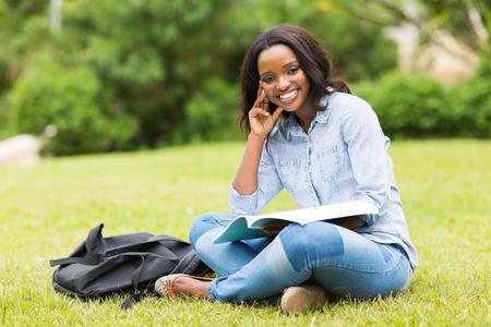 mujer sentada: bella joven universitario africano sentado en la hierba Foto de archivo