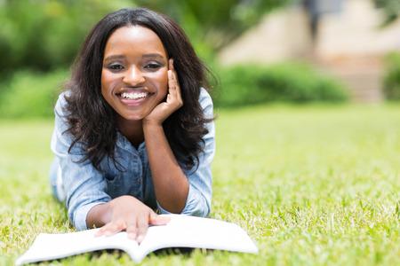 mujeres negras: joven mujer afroamericana tirado en el pasto y leyendo un libro Foto de archivo