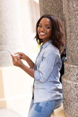 happy female african uni student using smart phone photo