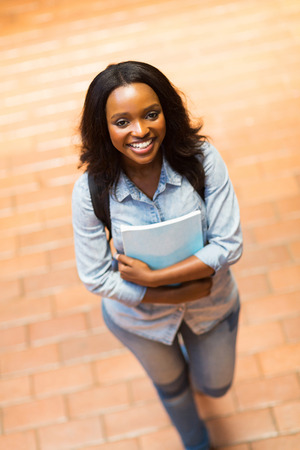 higher education: cheerful young african american college girl walking on campus
