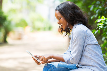 sms message: happy african american woman with smart phone listening music Stock Photo