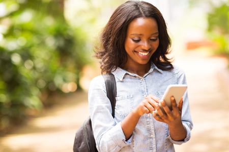 sms message: happy young african american uni student using cell phone
