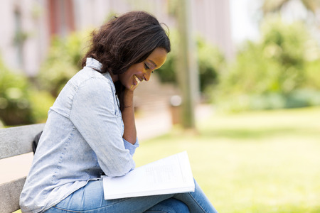 uni: smart african uni student reading a book Stock Photo