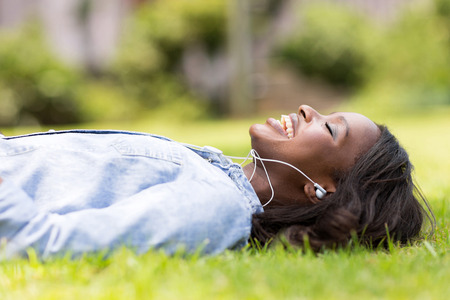 earphone: cheerful african woman lying on grass listening to music outdoors
