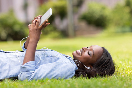 relajado: Mujer africana relajado tumbado en la hierba escuchando m�sica Foto de archivo