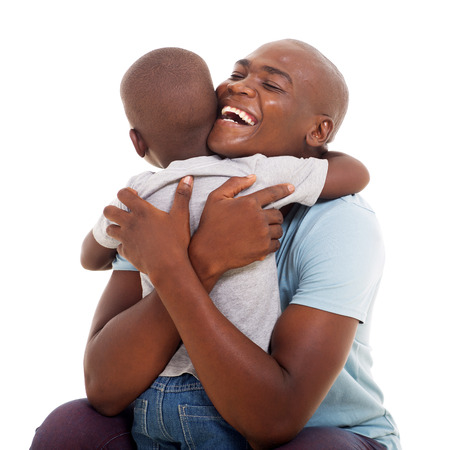 hugging: cheerful african american man hugging his son isolated on white background