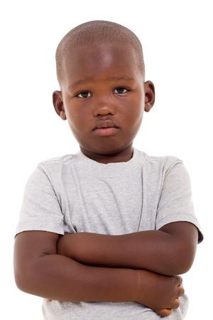 недовольны немного африканского мальчика со скрещенными руками на белом фоне Фото со стока