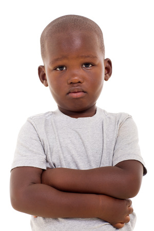 mirada triste: poco muchacho africano descontentos con los brazos cruzados sobre fondo blanco Foto de archivo