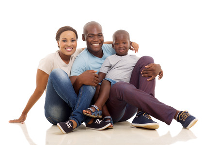 full length portrait: beautiful african family sitting on the floor isolated on white