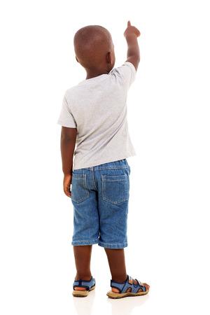 garcon africain: Vue arrière du petit garçon africain pointant sur fond blanc