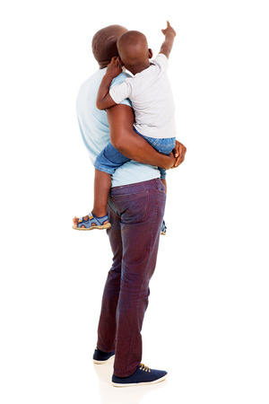 rear view of african american father and son pointing copy space