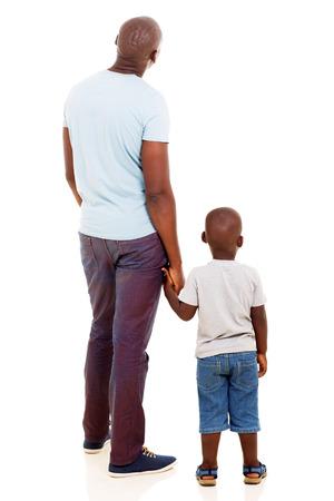looking at view: vista posteriore di giovane uomo africano con suo figlio isolato su sfondo bianco