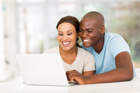 happy young african couple using laptop computer at home