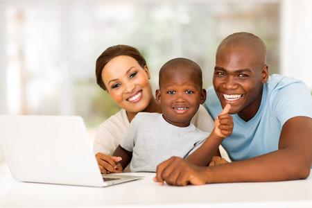 persona alegre: lindo chico africano que da el pulgar para arriba con los padres en el hogar
