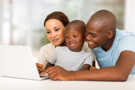 tecnología informatica: adorable joven afroamericano familia usando la computadora portátil en casa Foto de archivo