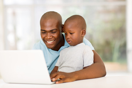 lovely young african man using laptop with his son at home