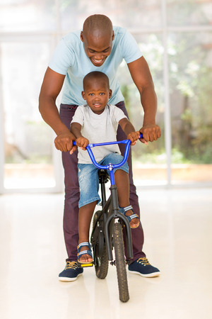 kid portrait: happy african man helping his son to ride a bike indoors