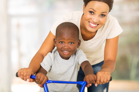 cheerful african mother teaching son to ride a bike