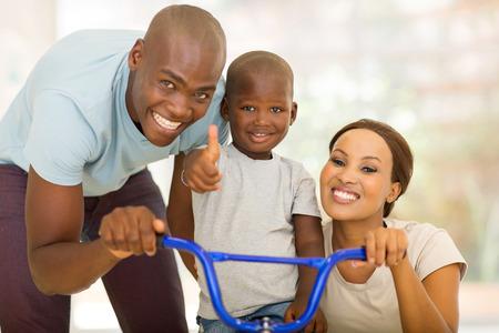 alegres padres africanos jóvenes ayudando a hijo a andar en bicicleta en interiores Foto de archivo