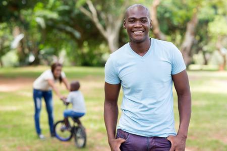 afroamericanas: hombre afroamericano hermoso que se coloca delante de la familia al aire libre
