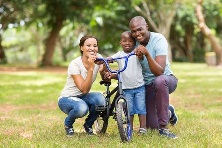 niños en bicicleta: retrato de la joven linda familia africana de tres al aire libre