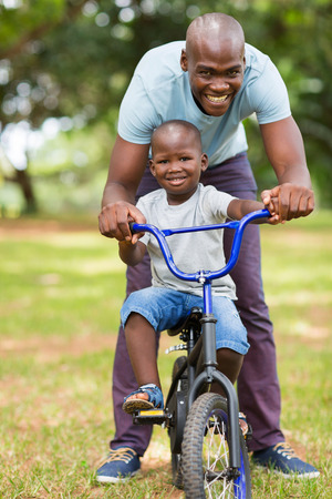 loving african father helping son ride a bike outdoors