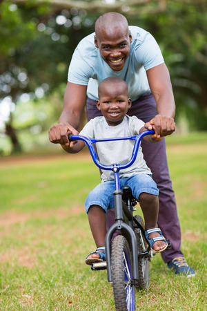 cheerful african american man teaching son to ride a bicycle at the park Stock Photo