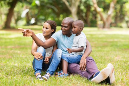 vacations: beautiful african family sitting on grass in the park Stock Photo