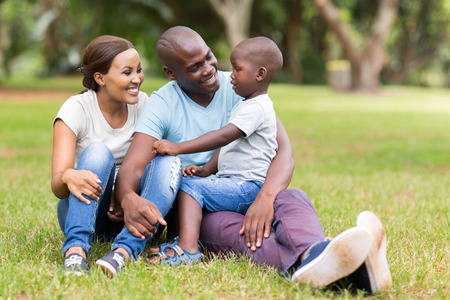 african american: young african family of three sitting together outdoors Stock Photo