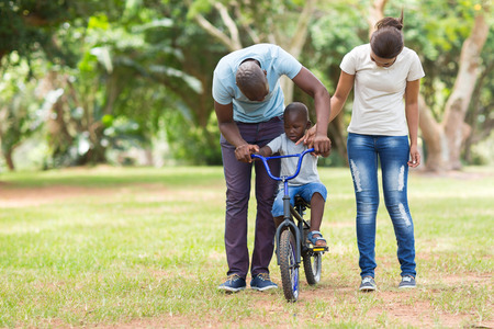 niños en bicicleta: encantadora joven familia africana tener tiempo de calidad al aire libre