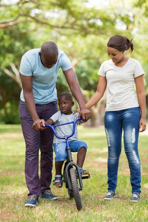 negras africanas: los padres j�venes que ense�an a su hijo a andar en bicicleta en el parque Foto de archivo