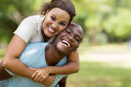 attractive young black couple piggybacking outdoors 写真素材