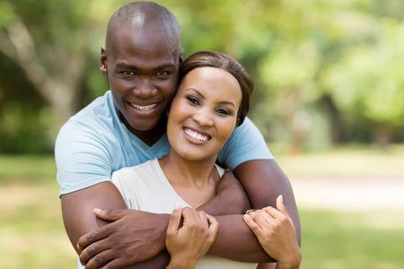 african american couple: good looking african man hugging girlfriend outdoors