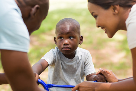 unhappy family: cute young african family playing outdoors
