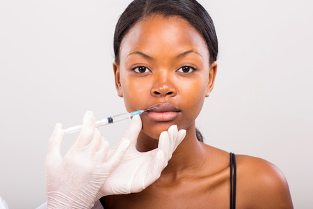 pretty young african woman receiving cosmetic injection in lips