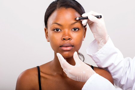 correction lines: portrait of african woman before marking her face for face lifting Stock Photo