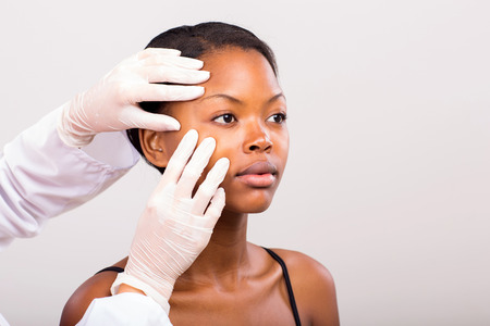 beauty surgery: dermatologist checking young african american woman face skin on plain