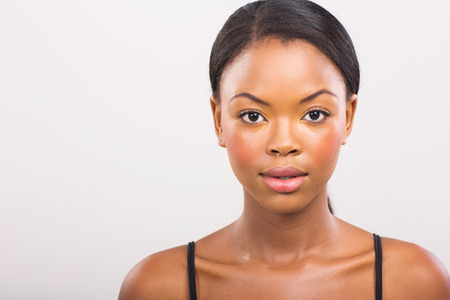 woman face close up: gorgeous african girl with natural makeup on plain