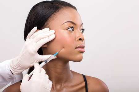 cosmetic surgery: african american woman face lifting on her cheek